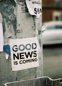 "Adesivo con la scritta ""Good News is coming"" attaccato ad un palo"