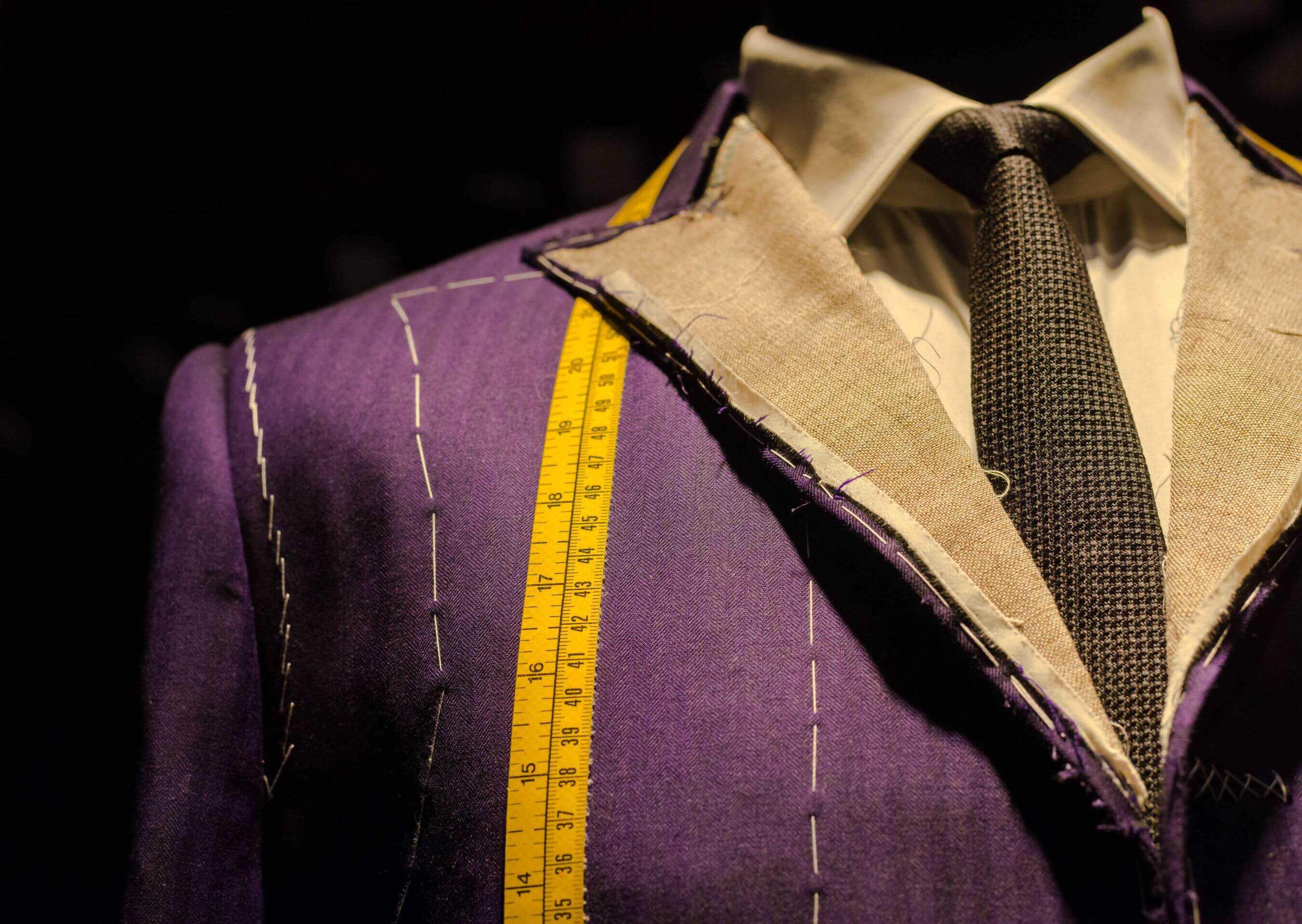Fotografia della parte superiore di una giacca imbastita e un metro da sarto